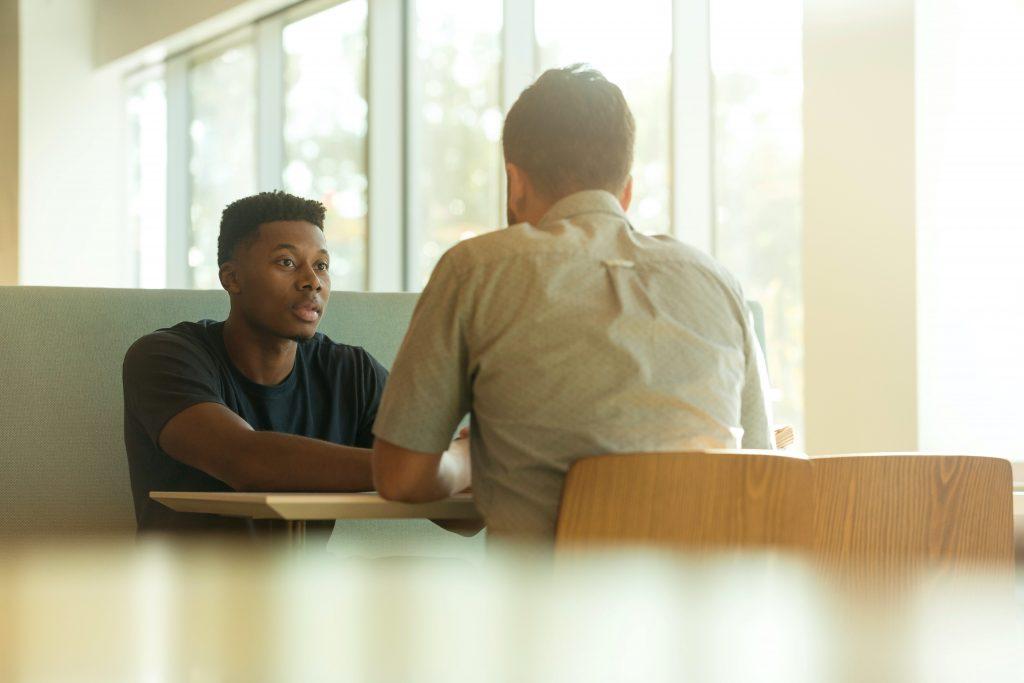 deux-hommes-dialoguent-assis-autour-d'une-table