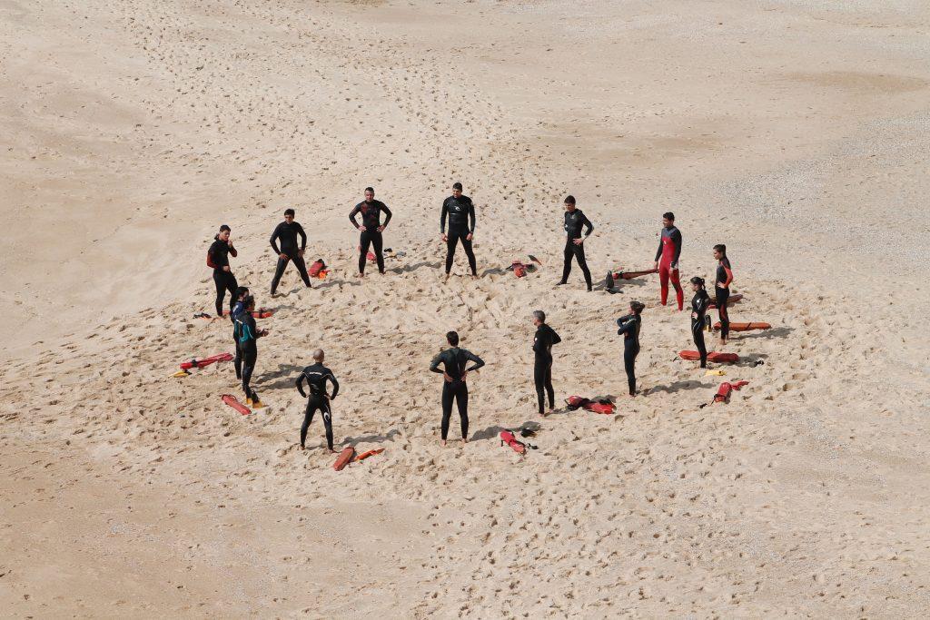 équipe de surfeurs regroupés en cercle sur le sable