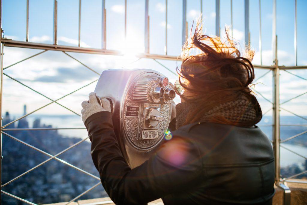 femme-de-dos-regardant-l'horizon-à-travers-des-jumelles